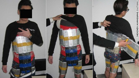 Photos released by customs authorities show dozens of neatly shrink-wrapped shiny iPhones strapped around the man's body.