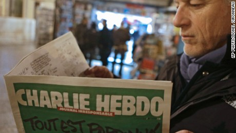 "Jean Paul Bierlein reads the new Charlie Hebdo outside a newsstand in Nice, southeastern France, Wednesday, Jan. 14, 2015. In an emotional act of defiance, Charlie Hebdo resurrected its irreverent and often provocative newspaper, featuring a caricature of the Prophet Muhammad on the cover that drew immediate criticism and threats of more violence. The black letters on the front page reads: ""All is forgiven."" (AP Photo/Lionel Cironneau)"
