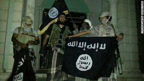 A picture taken with a mobile phone early on May 24, 2014 shows Al-Qaeda militants posing with Al-Qaeda flags in front of a museum in Seiyun, second Yemeni city of Hadramawt province, after launching a massive pre-dawn assault that killed at least 15 soldiers and police. The assault in Hadramawt, a jihadist stronghold that has seen large-scale attacks on the army in the past, came as troops pressed a month-old ground offensive against Al-Qaeda in Abyan and Shabwa provinces to the west. AFP PHOTO / STR        (Photo credit should read -/AFP/Getty Images)