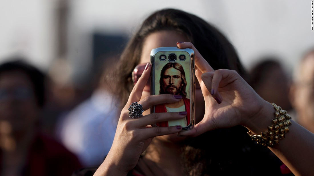 Jesus Christ is seen on the cell phone case of a woman waiting for the pope's arrival in Colombo.