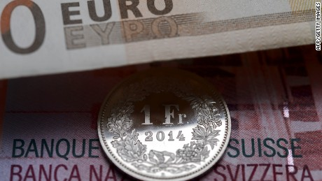 A Swiss coin is seen beneath a euro banknote on Januay 15, 2015 in Lausanne. In a shock announcement on January 15, Switzerland's central bank said it was ending a three-year bid to artificially hold down the value of the Swiss franc against the euro, in a move that immediately sent the safe haven currency soaring. AFP PHOTO / FABRICE COFFRINIFABRICE COFFRINI/AFP/Getty Images