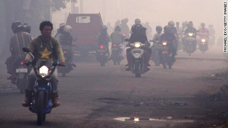 People wear masks as they ride through haze pollution on February 23, 2014 in Pontianak, Kalimantan, Indonesia.