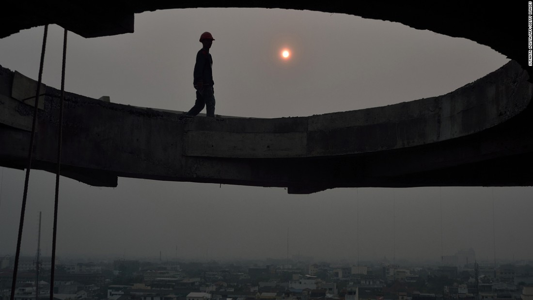 March 1 2014, In Medan, Indonesia, construction workers toil in the setting sun as smoke from fires in Riau province covers the region. The province was at the heart of a Southeast Asian smog crisis in 2013 and declared a state of emergency in February 2014 after being blanketed in a thick haze from forest fires.
