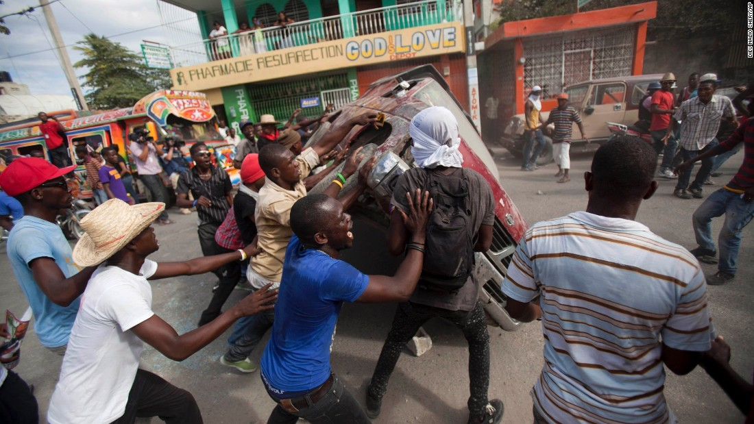 People in Port-au-Prince, Haiti, flip over a car to block a street during a protest demanding the resignation of President Michel Martelly on Sunday, January 11.