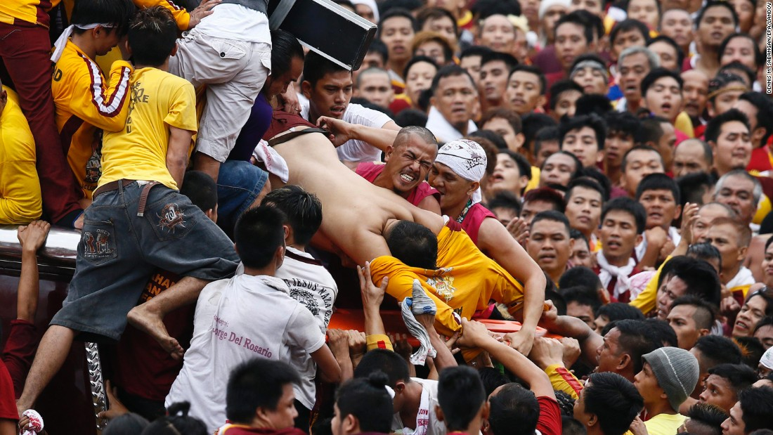People pull an injured devotee from the carriage of the statue of the Black Nazarene during a religious procession in Manila, Philippines, on Friday, January 9. Hundreds of thousands of Catholics joined the annual procession a week before Pope Francis visited the country.