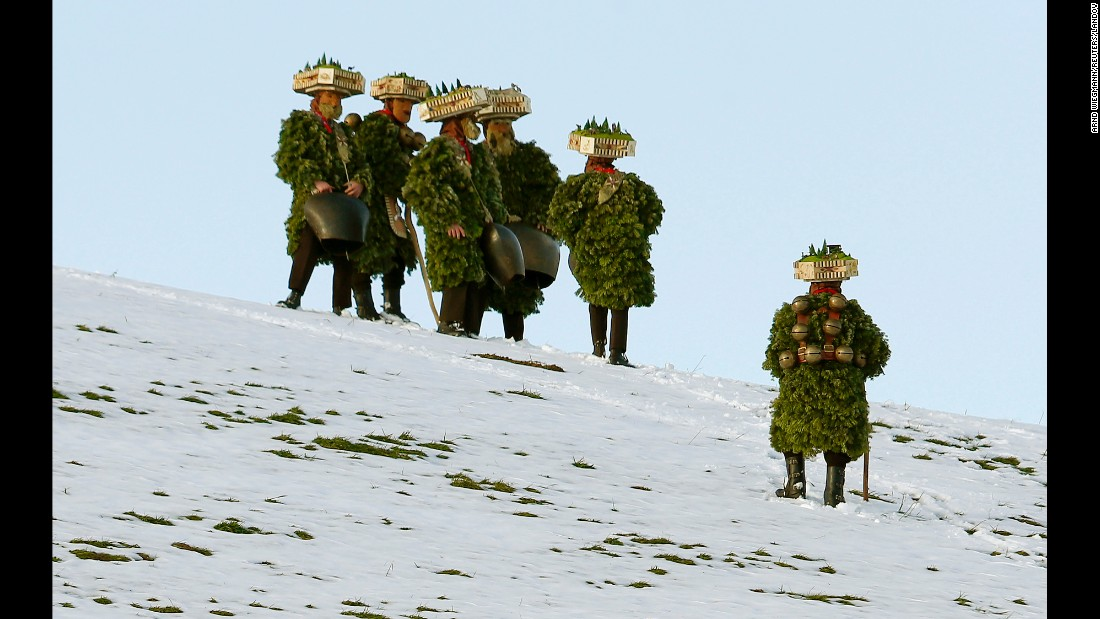 "Men dressed as ""Chlaeuse,"" figures that scare away evil spirits, carry bells on a meadow during the traditional Silvesterchlausen festival near Urnaesch, Switzerland, on Tuesday, January 13. Every year on December 31 and January 13, groups of Chlaeuse walk through the countryside of the canton of Appenzell Ausserrhoden."