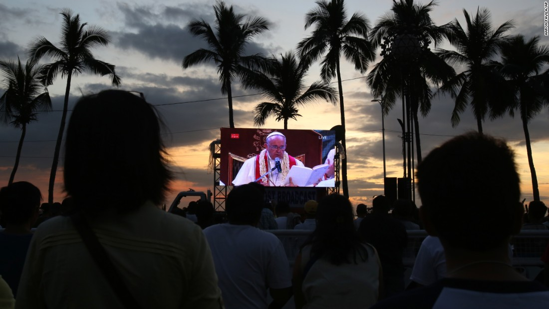 Crowds watch a live broadcast of Pope Francis during Mass on Friday, January 16,  in Manila, Philippines.