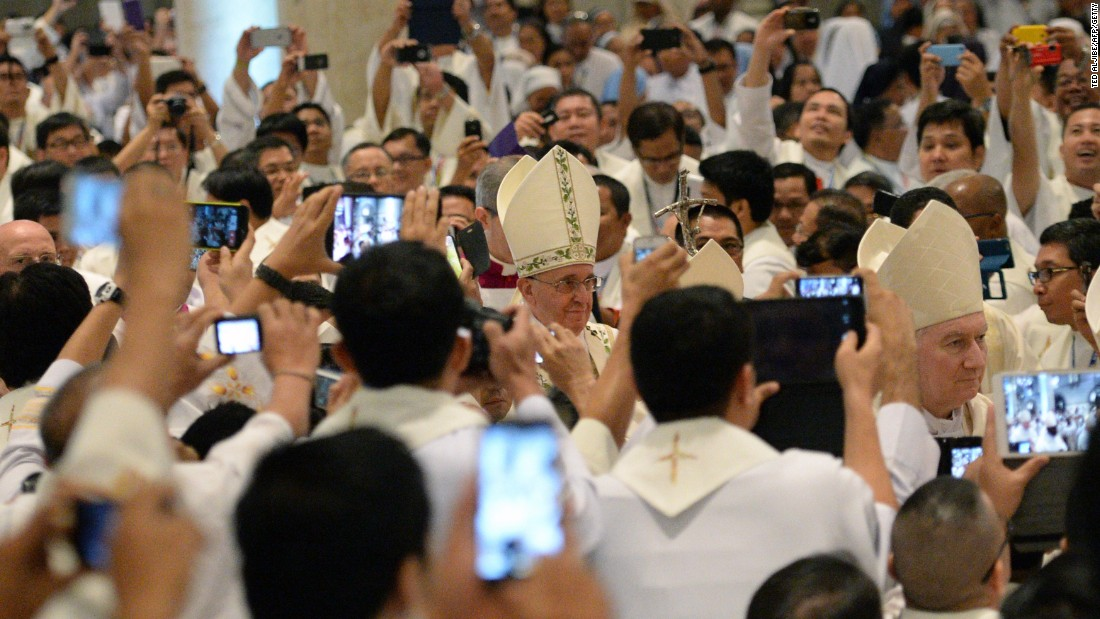 JANUARY 16 -- MANILA, PHILIPPINES: Catholic priests take smartphone photos of Pope Francis (C) as he enters for mass at the Manila cathedral.