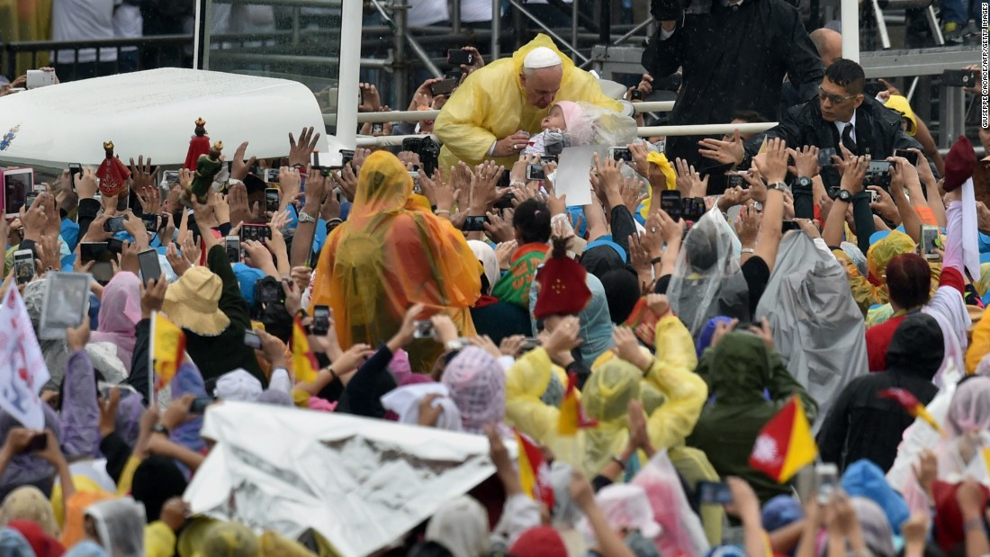 Pope Francis greets people and blesses their religious icons as he arrives to celebrate a mass at a park in Manila on January 18.