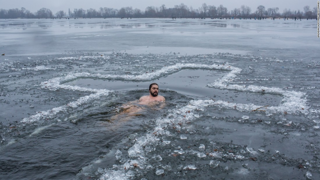 JANUARY 19 - KIEV, UKRAINE: A man bathes in the Dnieper River to mark Epiphany. Orthodox Christians celebrate the baptism of Jesus by plunging into the icy water to symbolically wash away their sins on a day when they believe all water becomes holy.
