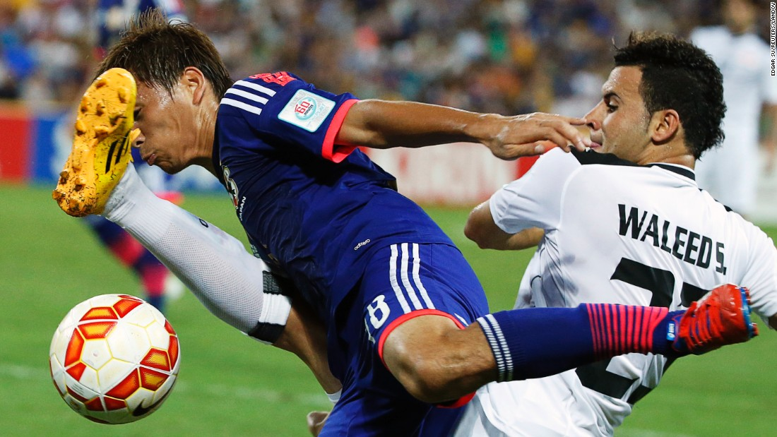 Japan's Takashi Inui, left, is tackled by Iraq's Waleed Salem Al-Lami during an Asian Cup match played Friday, January 16, in Brisbane, Australia. Japan, the defending champions, won 1-0 behind a goal from Keisuke Honda.
