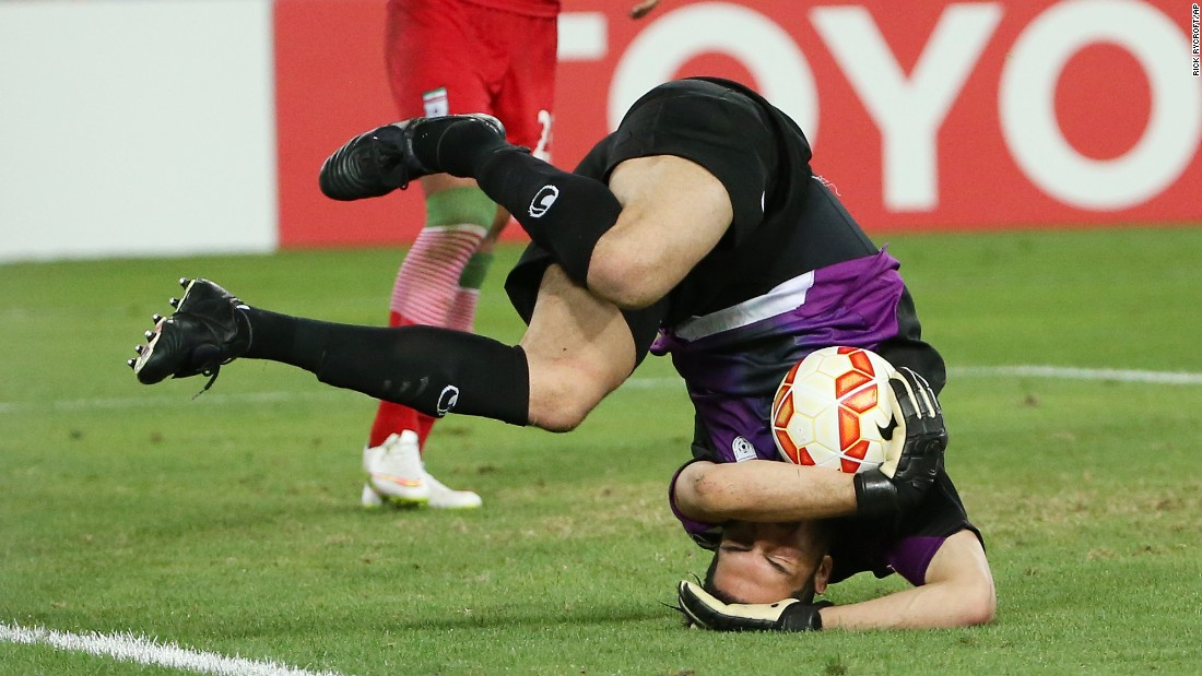 Iran goalkeeper Alireza Haghighi rolls on the ground after securing the ball during an Asian Cup match against Qatar on Thursday, January 15. Iran advanced to the quarterfinals of the tournament with a 1-0 victory.