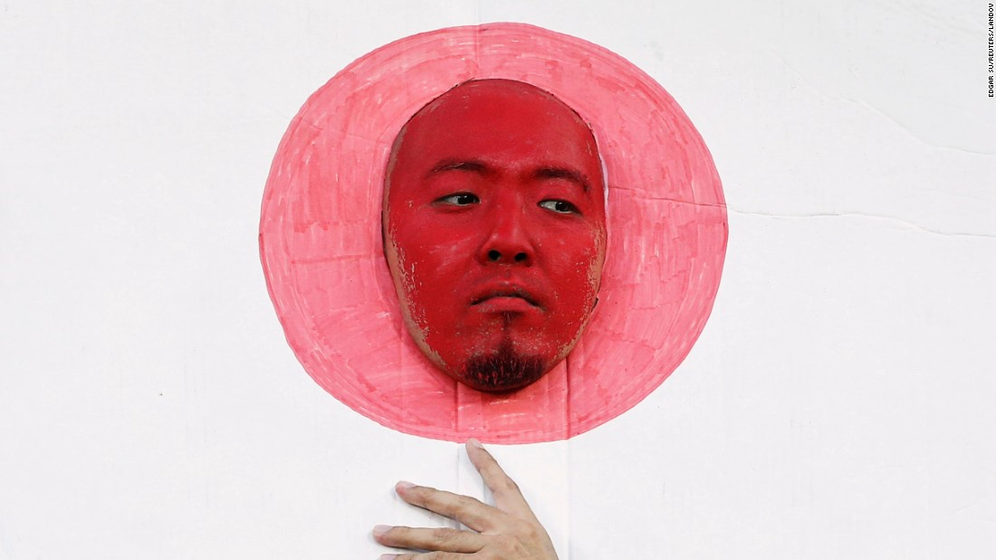 A face-painted Japan supporter sticks his head through a cutout of the Japanese flag before an Asian Cup soccer match on Friday, January 16.