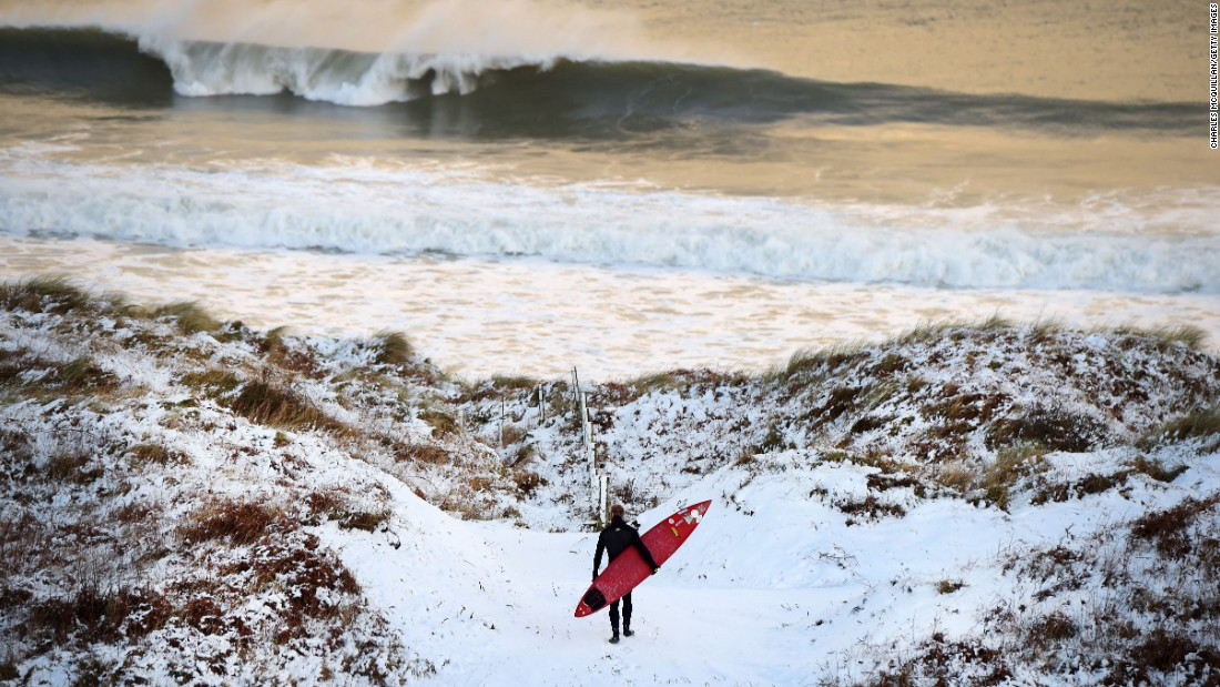 Pro surfer Alastair Mennie walks through snow as he makes his way toward the beach in Portrush, Northern Ireland, on Wednesday, January 14.
