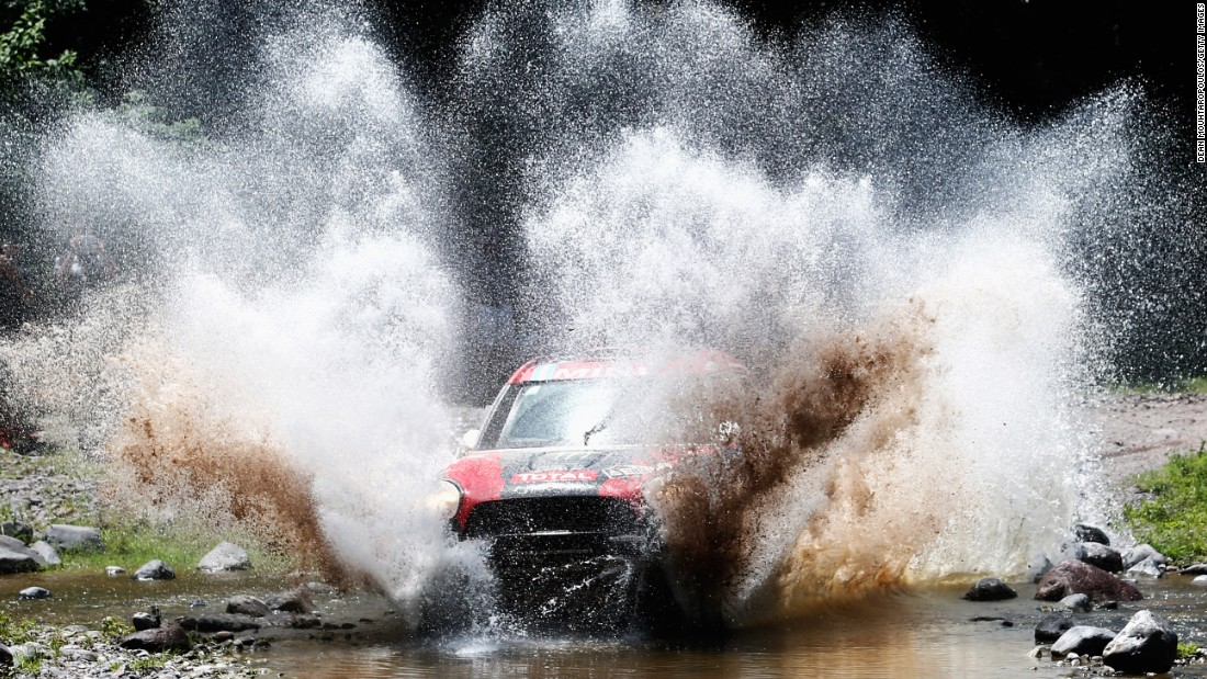 A car driven by Orlando Orly Terranova and Ronnie Graue splashes through muddy water on Thursday, January 15, during the 11th stage of the Dakar Rally. This stage was held in Argentina between the cities of Salta and Termas de Rio Hondo.