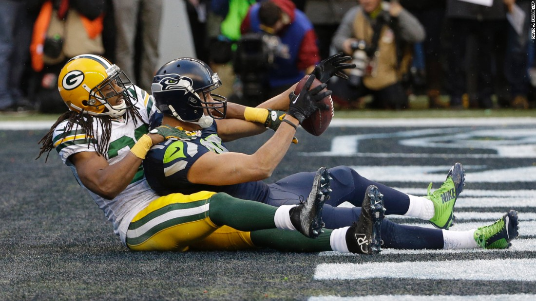 With Green Bay's Tramon Williams wrapped around him, Seattle wide receiver Jermaine Kearse holds on to the touchdown pass that won the NFC Championship on Sunday, January 18.
