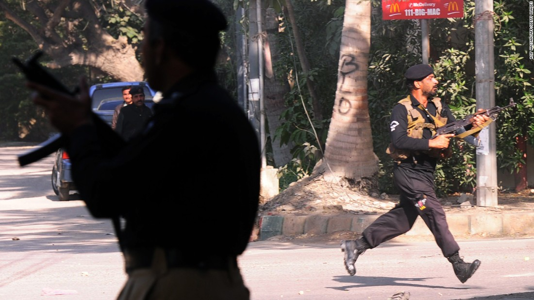Police officers chase after protesters near the French Consulate in Karachi on January 16.