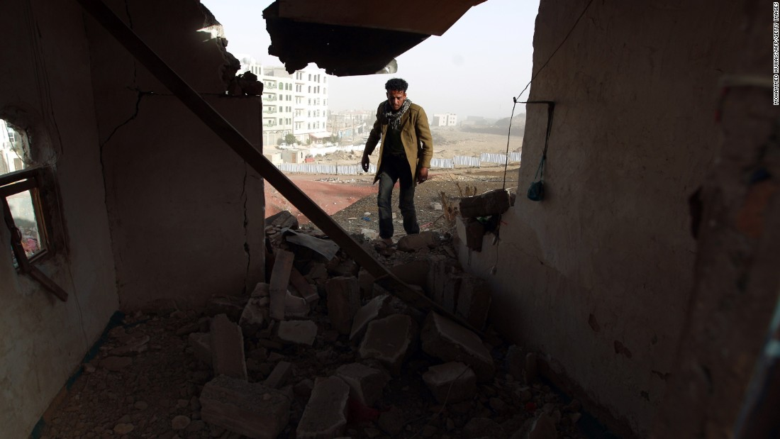 A man walks inside a heavily damaged house near the presidential palace on Tuesday, January 20.