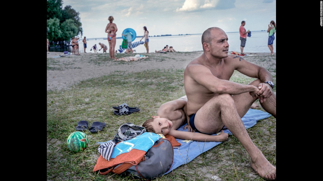Gyorgg Lakatos sits with his son Sebastain on a beach in Cherkasy by the Kremenchuk Reservoir on the Dnieper River.