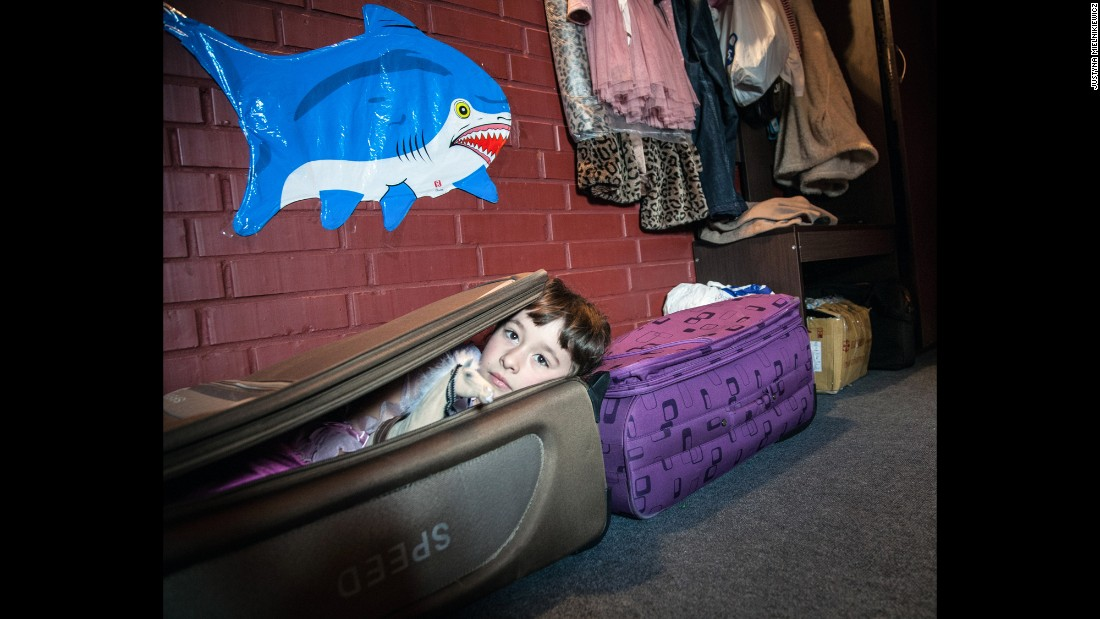 A girl lies in a suitcase her mother and grandmother brought with them while leaving Donetsk.