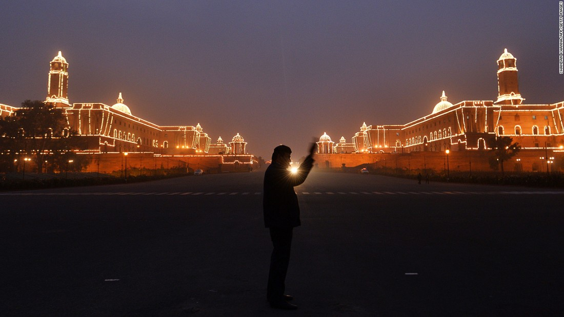 JANUARY 21 - NEW DELHI, INDIA: A policeman directs the traffic in front of the illuminated Central Secretariat building. India will celebrate its 65th Republic Day on January 26 with a large military parade.