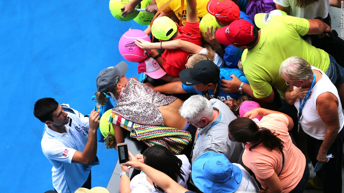 Despite the hot temperatures, Djokovic stayed on court to sign autographs. He's bidding for a fifth Australian Open title.