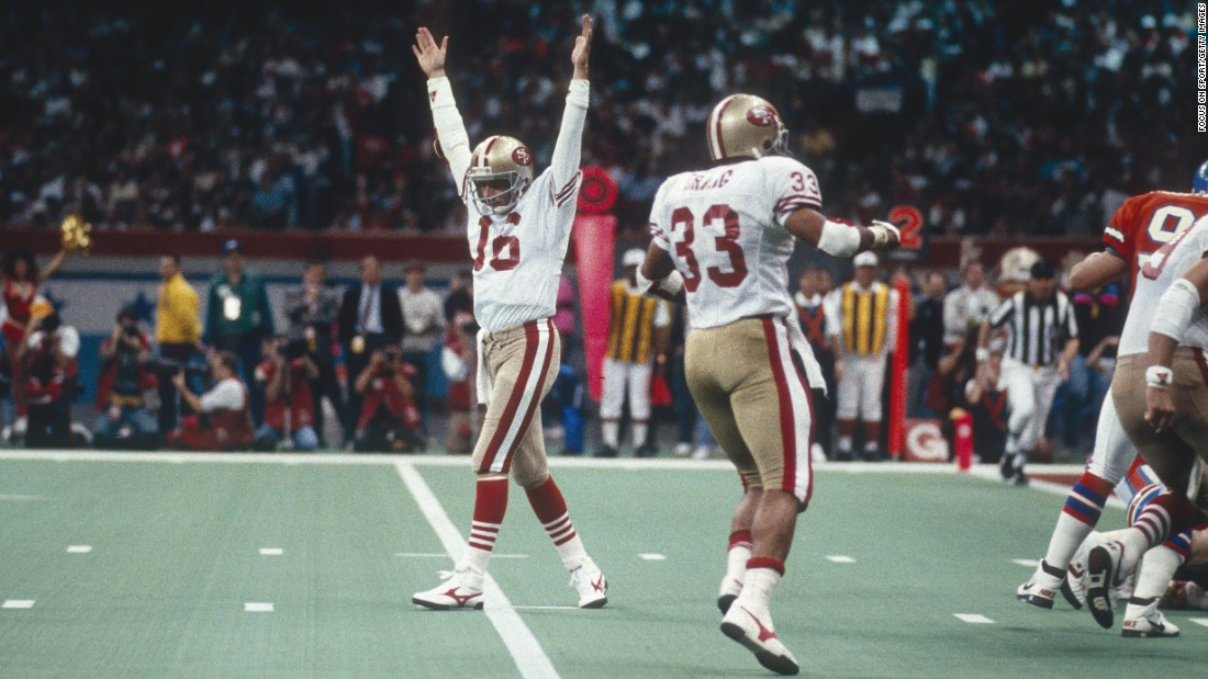 San Francisco quarterback Joe Montana raises his arms in celebration after a 49ers touchdown in Super Bowl XXIV. Montana had 297 yards passing and five touchdowns as the 49ers defeated Denver 55-10. It was the biggest blowout in Super Bowl history. Montana collected his third MVP award, and the 49ers capped a glorious run with four titles in nine years.