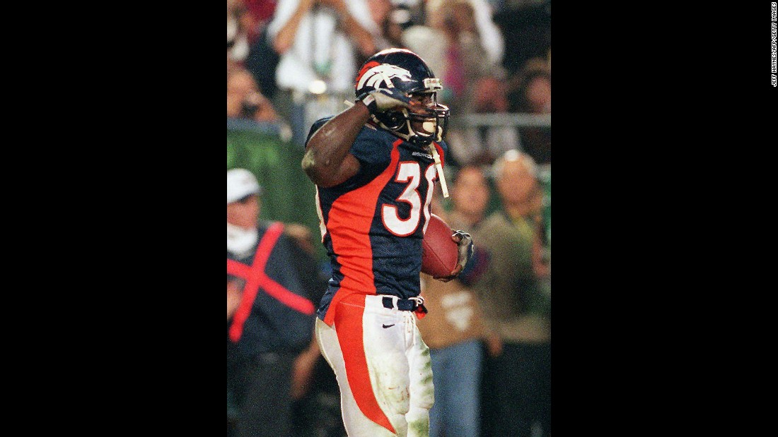 "Denver Broncos running back Terrell Davis does his signature ""Mile High Salute"" after scoring a touchdown against Green Bay in Super Bowl XXXII. Davis rushed for 157 yards and three touchdowns on his way to winning MVP."