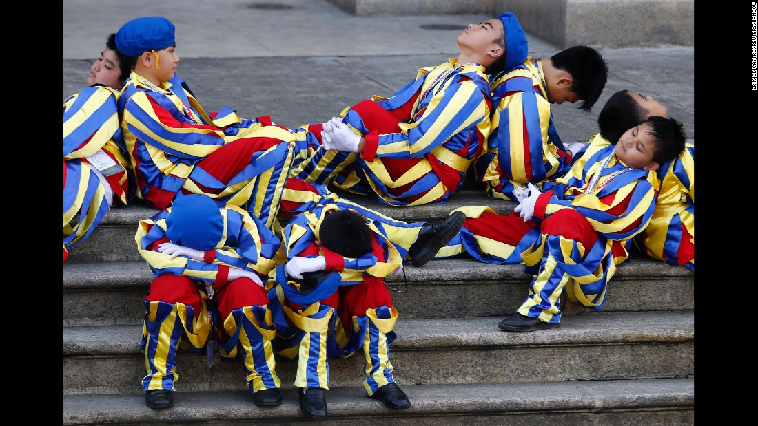 "Schoolchildren dressed as Swiss Guards rest outside the Manila Cathedral as they wait for Pope Francis to arrive in Manila, Philippines, on Friday, January 16. <a href=""http://www.cnn.com/2015/01/13/world/gallery/pope-in-asia/index.html"" target=""_blank"">See more photos from the Pope's weeklong trip to Asia</a>"