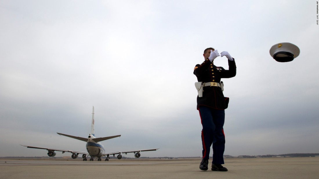 The jet exhaust from Air Force One blows the hat off U.S. Marine Cpl. Chaz Sorensen as it departs Andrews Air Force Base in Maryland on Wednesday, January 21.