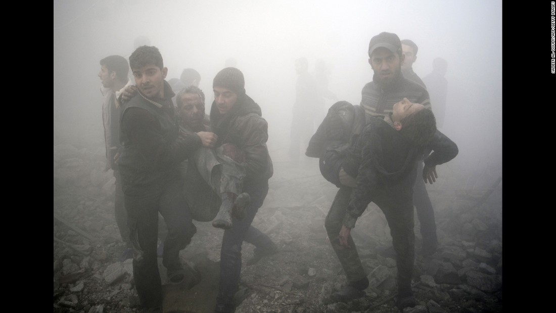 Syrian men carry wounded people after a reported airstrike on the rebel-held town of Douma, Syria, on Wednesday, January 21.