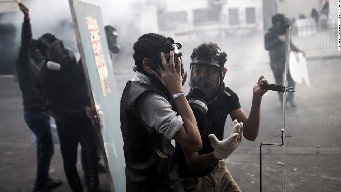 Protesters talk with gas masks on as they clash with police Friday, January 16, on the outskirts of Manama, Bahrain. They were demonstrating against the arrest of Sheikh Ali Salman, leader of the banned Shiite opposition movement Al-Wefaq.