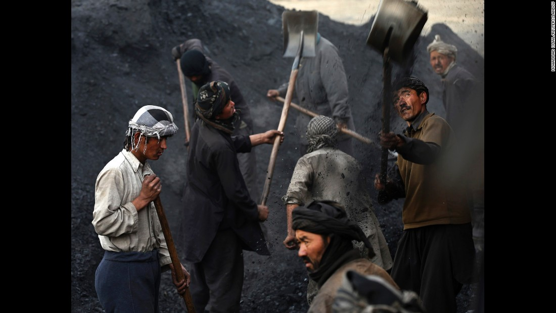 Laborers shovel coal onto a truck outside Kabul, Afghanistan, on Monday, January 19. Each laborer earns an average of $10 per day. Many of them left their families in the northern provinces to find work in the capital.