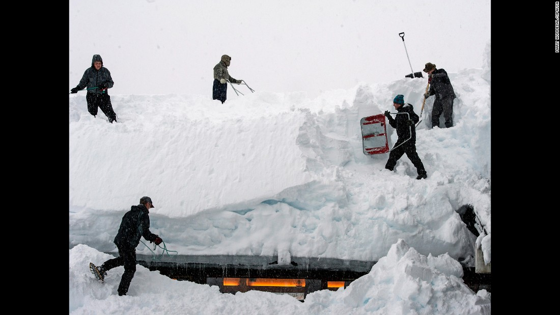 People remove snow from the roof of a hostel in Voss, Norway, on Friday, January 16.