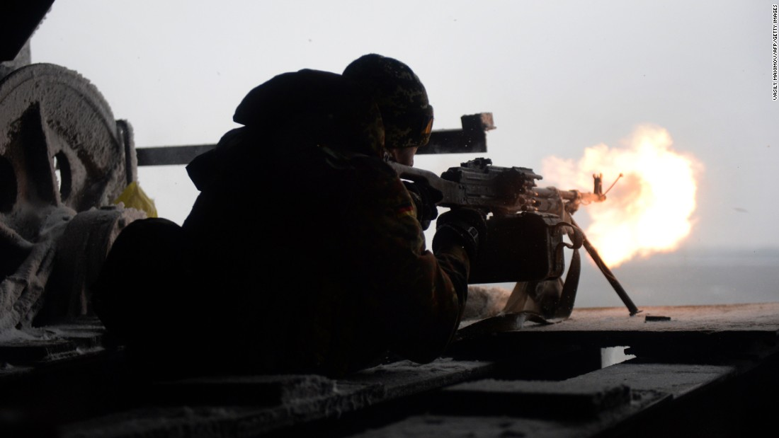 A Ukrainian volunteer fighter fires a machine gun at pro-Russian rebels near the village of Pisky, Ukraine, on Saturday, January 3.