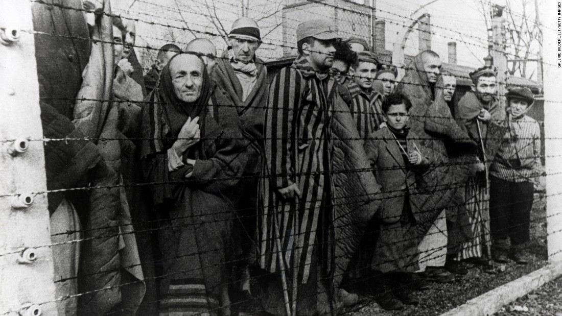 Survivors of Auschwitz stand behind a barbed wire fence. Some of the children are seen wearing adult clothing they were dressed in by Soviet soldiers.