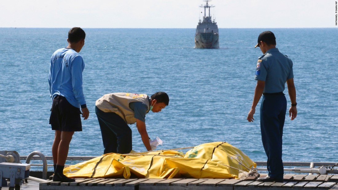 Crew members inspect body bags on the deck of a ship in the Java Sea on Friday, January 23.