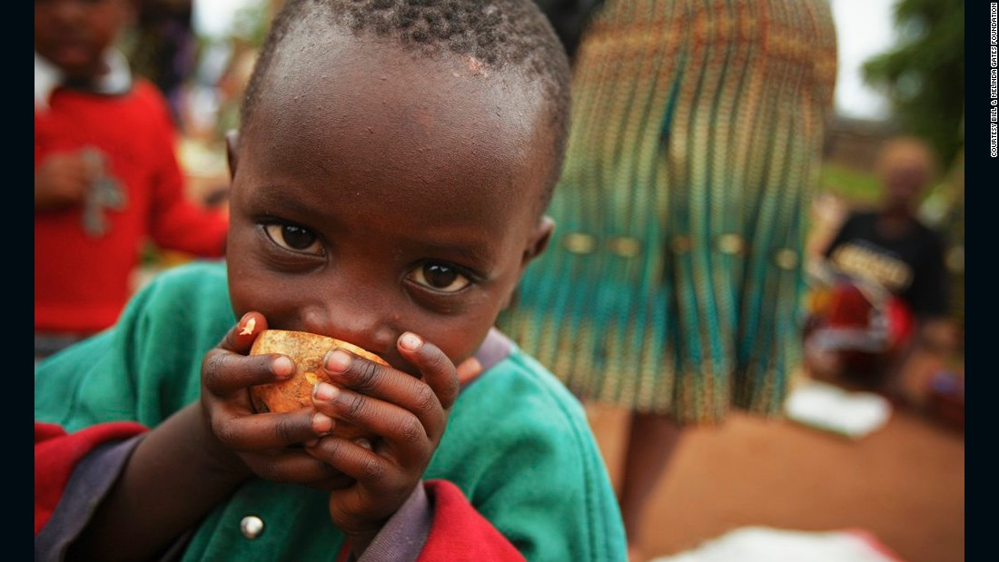 A young boy samples an orange-fleshed sweet potato in a busy market in Mwasonge, Tanzania.