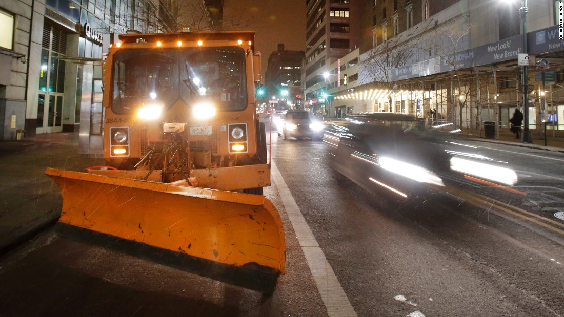 A New York City snowplow, loaded with salt, sits in midtown Manhattan as light snow falls on January 26.