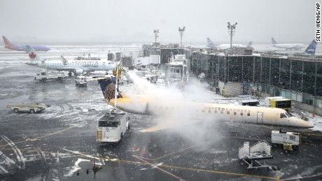 A plane is de-iced at LaGuardia Airport in New York, Monday, Jan. 26, 2015. Airlines canceled thousands of flights into and out of East Coast airports as a major snowstorm packing up to 3 feet of snow barrels down on the region. (AP Photo/Seth Wenig/AP)