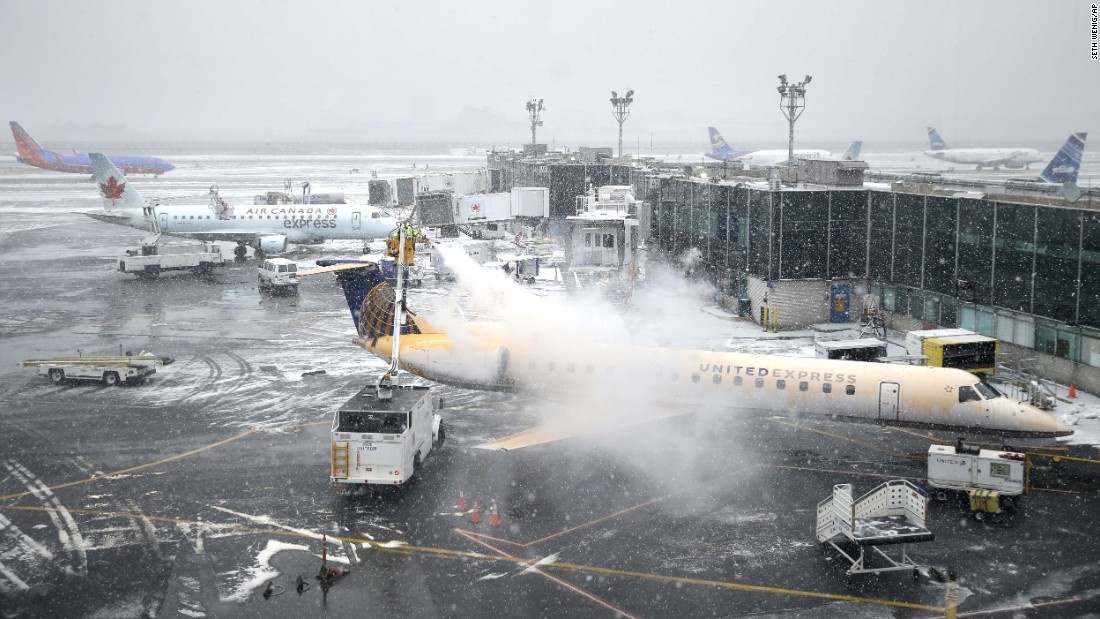 A plane is de-iced at New York's LaGuardia Airport on January 26. Thousands of flights were canceled in anticipation of the storm.