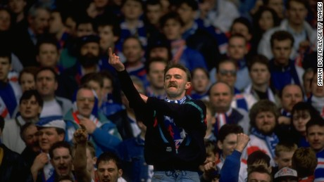 A Rangers fan gestures towards Celtic supporters during an Old Firm game in 1991.