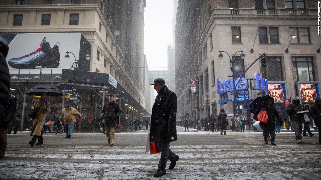 People walk near Penn Station on New York's Seventh Avenue while a major snowstorm begins on January 26.