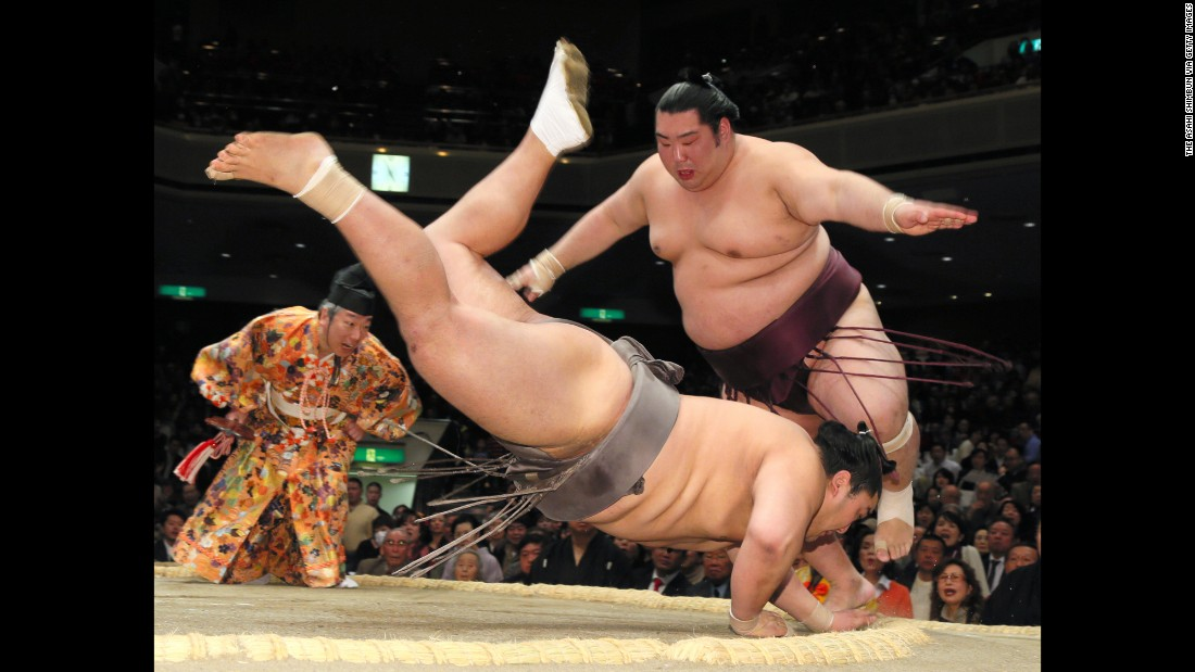 Tokushoryu, right, jumps as his opponent, Okinoumi, falls during a sumo match in Tokyo on Wednesday, January 21.