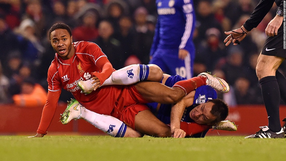 Liverpool's Raheem Sterling, left, and Chelsea's John Terry get tangled up during a League Cup semifinal match Tuesday, January 20, in Liverpool, England. Sterling scored a goal in the match as the two teams tied 1-1.