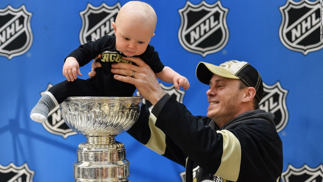 Trevor Young removes his 10-month-old son, Donovan, from the Stanley Cup after posing for a photograph Thursday, January 22, in Columbus, Ohio. The trophy was on display for the fans as part of the NHL's All-Star Weekend.
