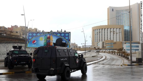 Libyan security forces and emergency services surround Tripoli's central Corinthia Hotel (R) on January 27, 2015 in the Libyan capital. The hotel was reportedly attacked by Islamist gunmen today and gunfire was heard, an AFP photographer reported.