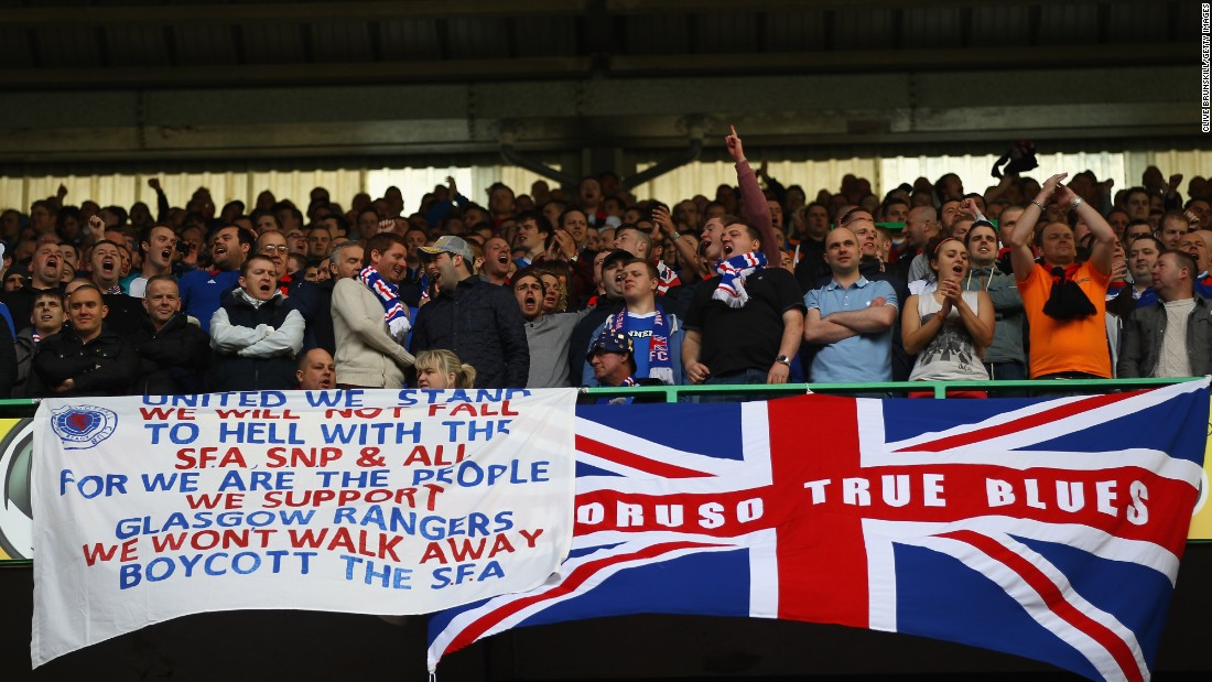 Rangers fans see things differently with the vast majority of the opinion that they are the same club as it was the company that ran the club and not the club itself that was liquidated. Here, a group of Rangers fans display a Union Jack and a banner emphasizing their support for the club at Celtic Park in 2012.