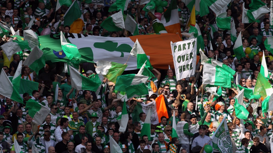 Celtic fans wave flags and an Irish tricolor at an Old Firm game at Ibrox Stadium in 2012. Historically, Celtic has been the club of Glasgow's Irish Catholic diaspora while Rangers the club of the city's majority Protestant population.