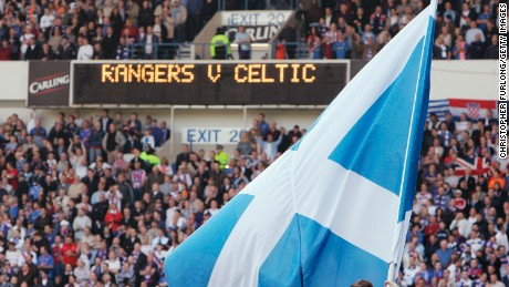 A Scottish saltire is waved before an Old Firm game at Ibrox.